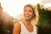 African-American woman with long dark hair and white t-shirt, smiling in the bright sunlight, soul healing
