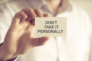 Businessman holding DONT TAKE IT PERSONALLY message card