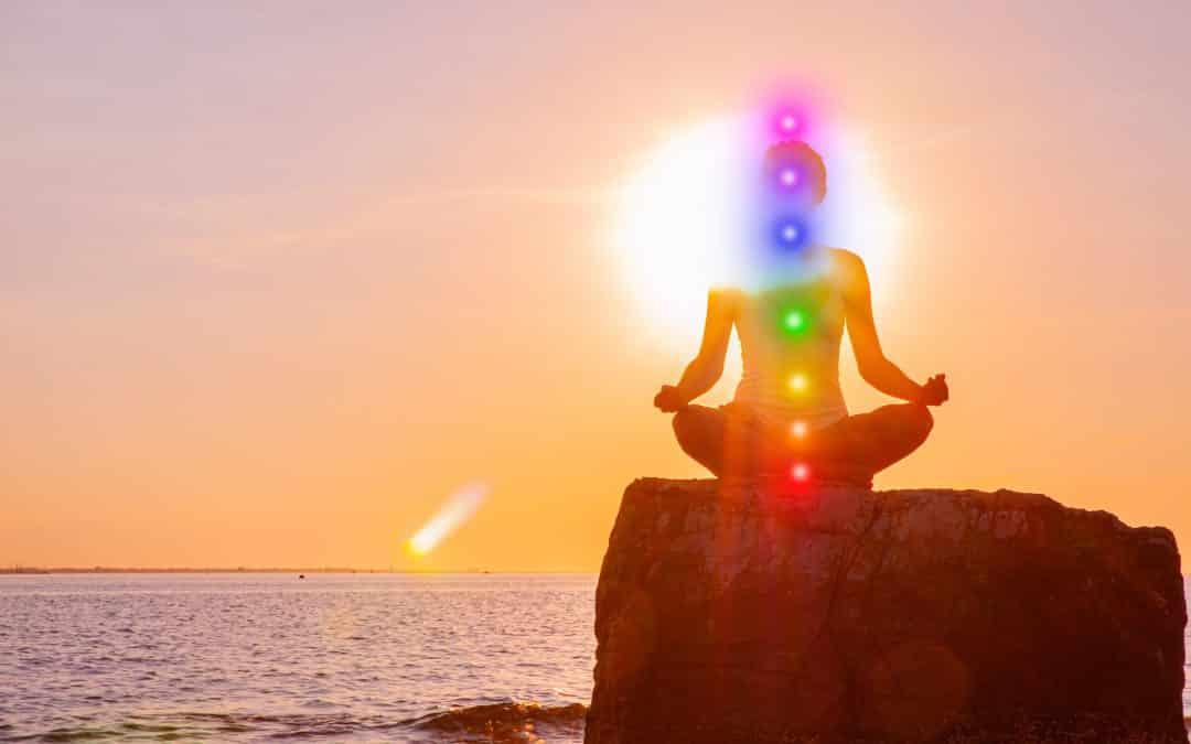 Woman is meditating with glowing seven chakras on stone at sunset. Silhouette of woman is practicing yoga on the beach, 3 key elements for energy healing - part II