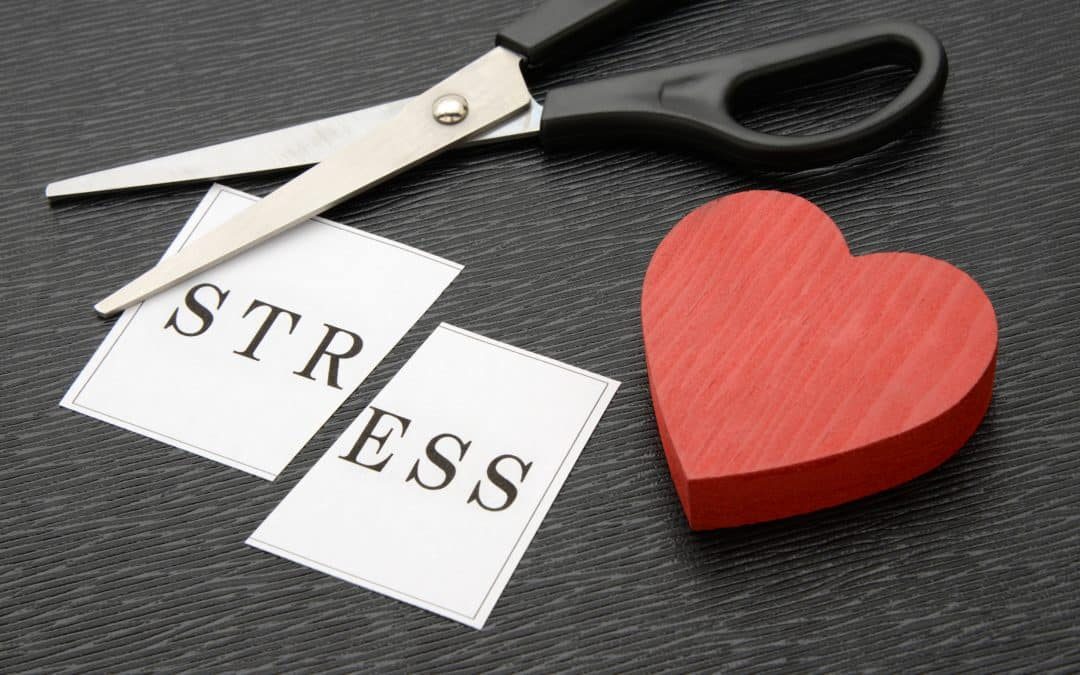 scissors cutting the word stress in two parts, red wooden heart, how to release stress