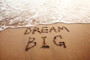 on the beach, ocean water over the sand, written in the sand, dream big, How to Manifest When Things Fall Apart