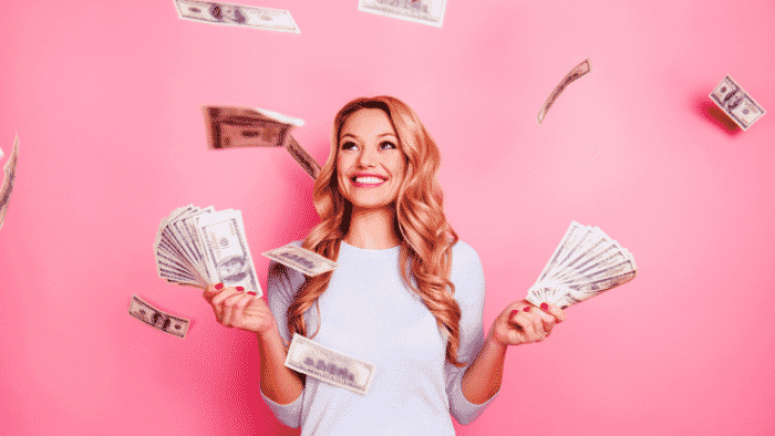 woman with long blonde hair, red lipstick, white long sleeves shirt and beautiful face holding dollar signs in her hands and throwing them in the air, smiling, What to Do When Manifesting Doesn't Last?