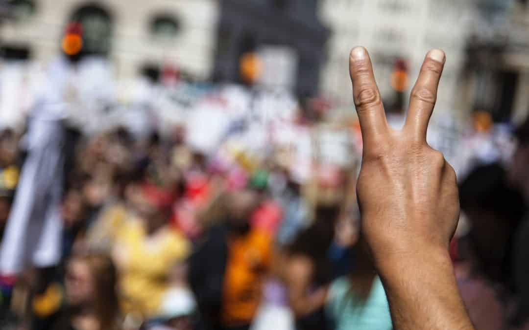 A raised hand of a protestor at a political demonstration, 3 Energy Alchemy Tools to Transmute Tension